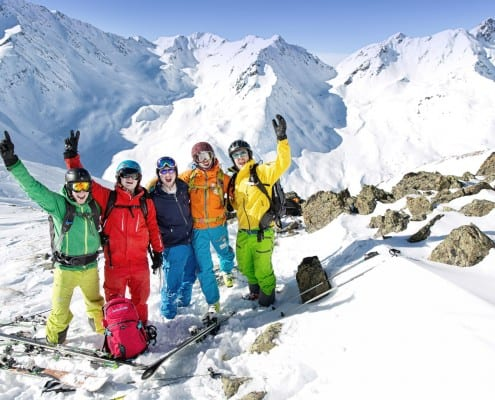 Group of freeride skiers in the mountains with an off-piste guide