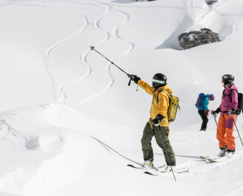 Off-piste ski guide with guest skiers in snow